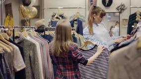 La mujer bonita joven que busca la nueva ropa en un estante y una dependienta joven le trae una camiseta en una tienda de ropa almacen de metraje de vídeo