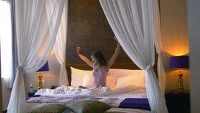 La mujer bonita joven que despierta en la cama blanca estira y los saltos alegres en dormitorio 3840x2160 almacen de metraje de vídeo