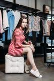 La mujer bonita joven que elige, intentando y vestido de las compras en la ropa de la tienda Bandera para la ropa de la tienda en fotos de archivo