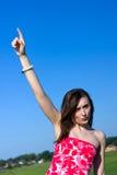 La mujer bonita joven señala su dedo en el cielo Fotos de archivo
