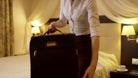 La mujer bonita joven se sienta en la cama y pone cosas de la maleta negra almacen de metraje de vídeo