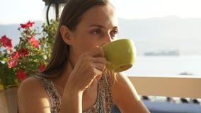 La mujer bonita joven se sienta en un café que contempla hermosas vistas de la bahía del mar almacen de video