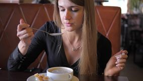 La mujer bonita joven se sienta en un café y apetitosamente come una sopa poner crema caliente almacen de video