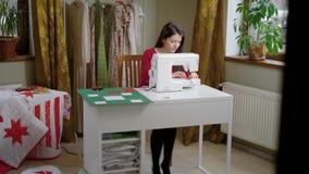 La mujer bonita joven trabaja en taller de la materia textil metrajes