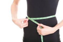 La mujer bonita muestra su aislante de las cintas de la medida de la pérdida de peso que lleva imagen de archivo