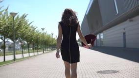 La mujer bonita presenta en sombrero rojo afuera en un día soleado almacen de metraje de vídeo