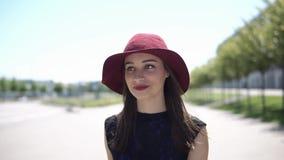 La mujer bonita presenta en sombrero rojo afuera en un día soleado metrajes