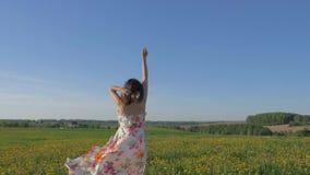 La mujer bonita que camina en un campo amarillo floreciente en un vestido aumenta los brazos para arriba almacen de video