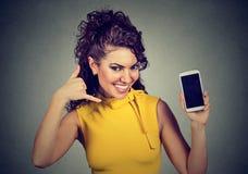 La mujer bonita que lleva a cabo la demostración del teléfono móvil me llama gesto de mano Imagenes de archivo