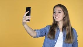 La mujer bonita que tomaba Selfie con Smartphone aisló en fondo amarillo almacen de video