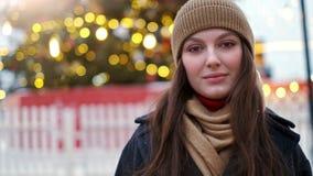 La mujer bonita se coloca en el cuadrado de ciudad entre decoraciones de la Navidad y miradas derecho en la cámara almacen de video