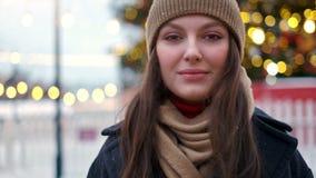 La mujer bonita se coloca en el cuadrado de ciudad entre decoraciones de la Navidad y miradas derecho en la c?mara almacen de video