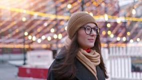 La mujer bonita se coloca en el cuadrado de ciudad entre decoraciones de la Navidad y miradas derecho en la c?mara metrajes