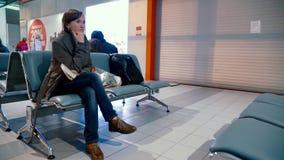 La mujer bonita se sienta en el aeropuerto almacen de video