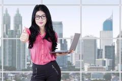 La mujer bonita sostiene el ordenador portátil y muestra el pulgar para arriba Fotografía de archivo libre de regalías