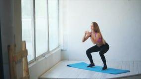 La mujer bonita y atlética hace posiciones en cuclillas profundas para consolidar las nalgas en el gimnasio metrajes
