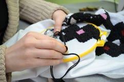La mujer borda a mano el bordado ucraniano en la tela blanca con los hilos negros y rosados de las lanas en un aro fotos de archivo libres de regalías