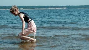 La mujer borracha camina en el agua en la playa con un vidrio de vino después de un partido almacen de video