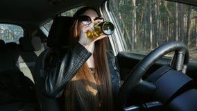 La mujer borracha hermosa bebe la cerveza detrás de la rueda, danzas en el coche metrajes