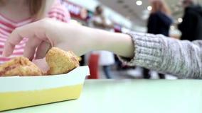 La mujer borrosa irreconocible que se sienta con su hijo por la tabla en la zona de restaurantes de la alameda y ellos están comi almacen de video