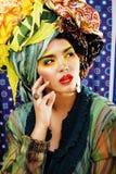 La mujer brillante de la belleza con creativo compone, muchos mantones en la cabeza l Fotos de archivo