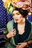 La mujer brillante de la belleza con creativo compone, muchos mantones en la cabeza l Imagen de archivo libre de regalías