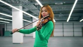 la mujer Bronce-cabelluda está tocando hábilmente el violín almacen de video