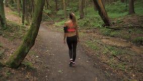 La mujer bronceada atlética va reservado a lo largo de Forest Road, vestido para activar metrajes