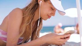 La mujer bronceada atractiva delgada relajada hermosa en bikini y el casquillo blanco con la bandera de Jack British de la unión  almacen de video