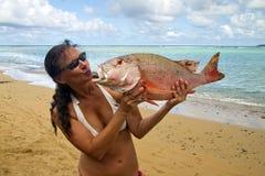La mujer bronceada envía un beso a un pescado enorme foto de archivo