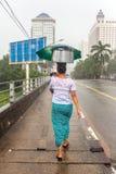 La mujer burmese no identificada lleva el pote del metal en su cabeza durante las fuertes lluvias en Rangún, Myanmar Imagenes de archivo