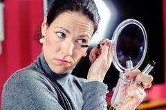 La mujer cabelluda oscura que mira en espejo y que se aplica compone Imágenes de archivo libres de regalías