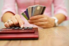 La mujer calcula cuánto coste o gasto tiene con las tarjetas de crédito Foto de archivo libre de regalías