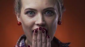 La mujer caliente con sorprender compone y la barra de labios roja está abriendo su boca con la expresión sorprendida, cámara len almacen de metraje de vídeo
