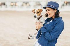 La mujer camina con el pequeño perro imagenes de archivo