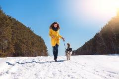La mujer camina con el perro en el bosque del invierno Fotografía de archivo