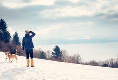 La mujer camina con su perro en la colina de la montaña Foto de archivo
