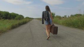 La mujer camina con una maleta en el camino almacen de video