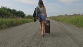 La mujer camina con una maleta en el camino almacen de metraje de vídeo