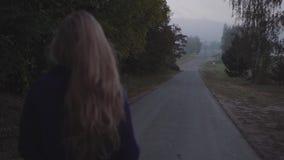 La mujer camina en el camino almacen de metraje de vídeo