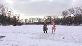 La mujer camina en el hielo en un bañador y descalzo almacen de metraje de vídeo