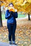 La mujer camina en el parque del otoño, recogiendo las hojas Retrato integral vertical Fotografía de archivo