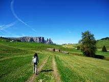 La mujer camina en un campo abierto verde Foto de archivo
