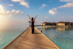 La mujer camina en un embarcadero de madera en los Maldivas foto de archivo libre de regalías