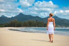 La mujer camina en una playa Imagen de archivo libre de regalías