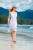 La mujer camina en una playa Foto de archivo