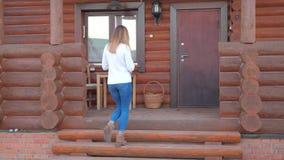 La mujer camina encima de los pasos al pórtico de una casa de madera y sostiene una taza de té metrajes