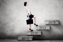 La mujer camina hacia los números 2017 en las escaleras Foto de archivo libre de regalías