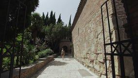 La mujer camina a lo largo de la avenida entre edificios de ladrillo viejos Complejo antiguo de la iglesia con la torre y el parq almacen de metraje de vídeo
