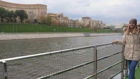 La mujer camina a lo largo de un terraplén del río y admira las hermosas vistas de la ciudad almacen de metraje de vídeo